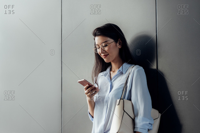Pretty Thai smiling woman standing by the grey wall holding a purse and looking at her smart phone.