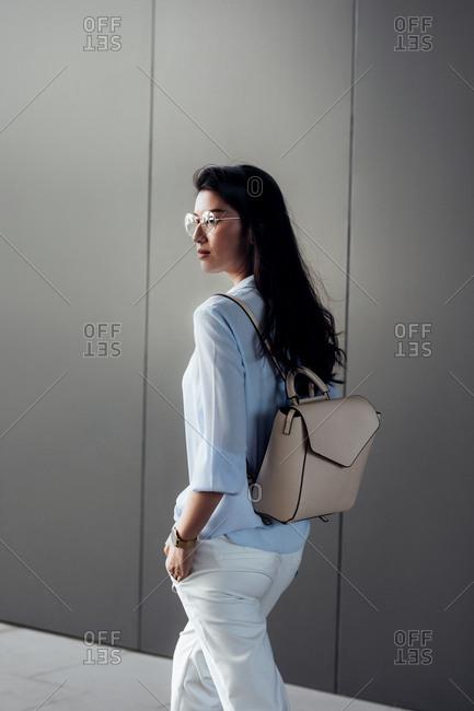 Elegant Thai woman walking with rucksack.