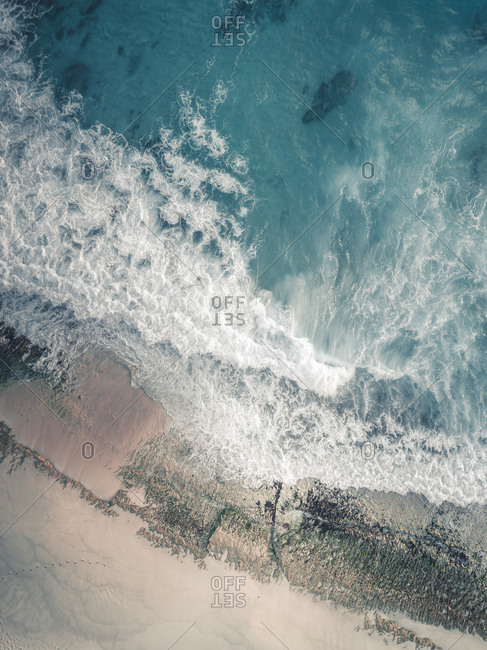 Aerial view of waves crashing into sandy beach, Seychelles, Africa