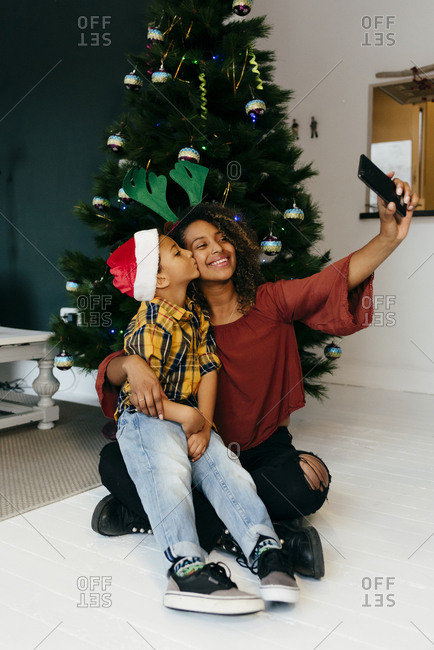 Funny black girl and kid disguised with Christmas accessories taking a self-portrait