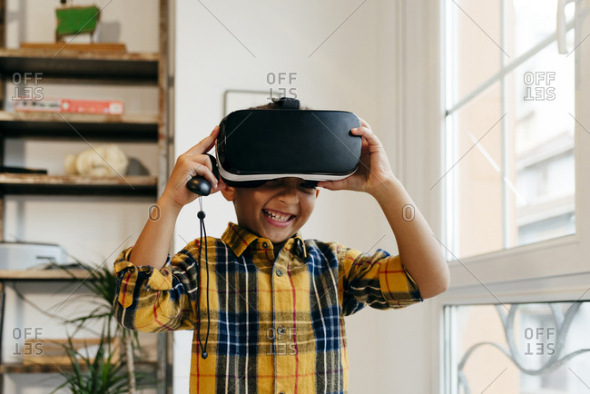 Cute black kid playing with VR glasses at home