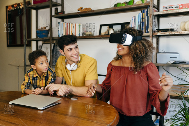 Multicultural couple with a kid playing with VR glasses at home