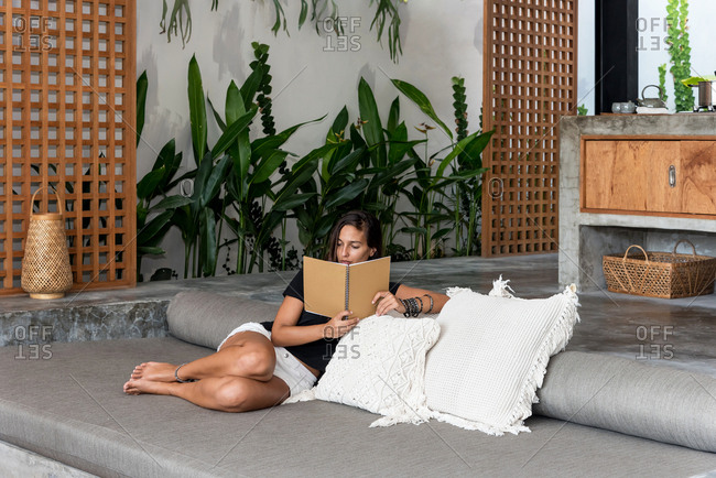 Brunette woman reading book on sofa in a luxury villa, Bali