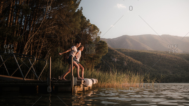 Two friends relaxing on a dock in a lake in a sunset of summer