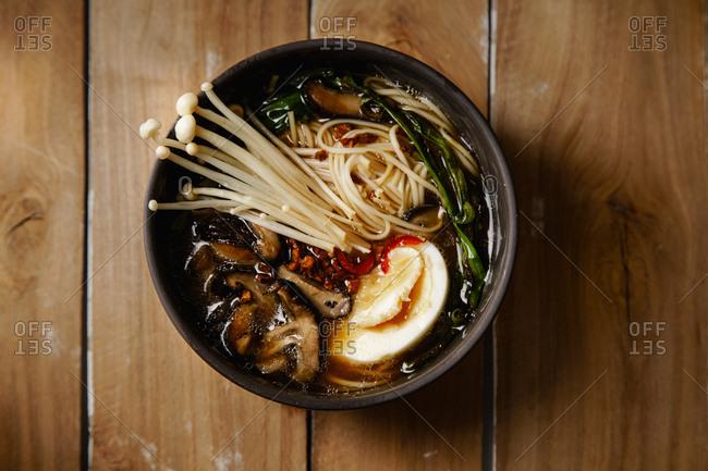 Top view shot of vegetarian ramen with enoki, oyster and shiitake mushrooms on wooden talbe