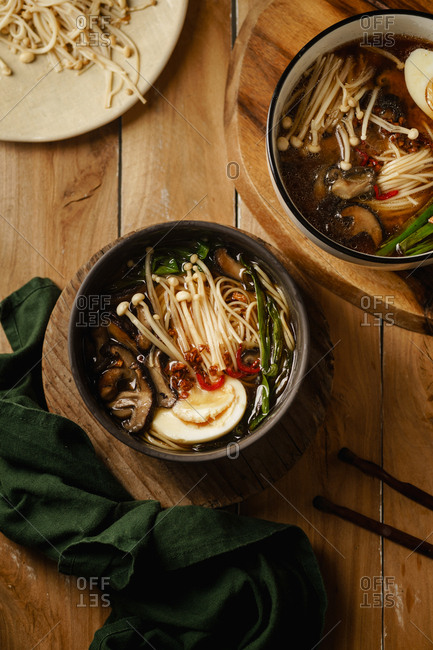 Top view shot of two bowls of vegetarian ramen with enoki, oyster and shiitake mushrooms on wooden talbe