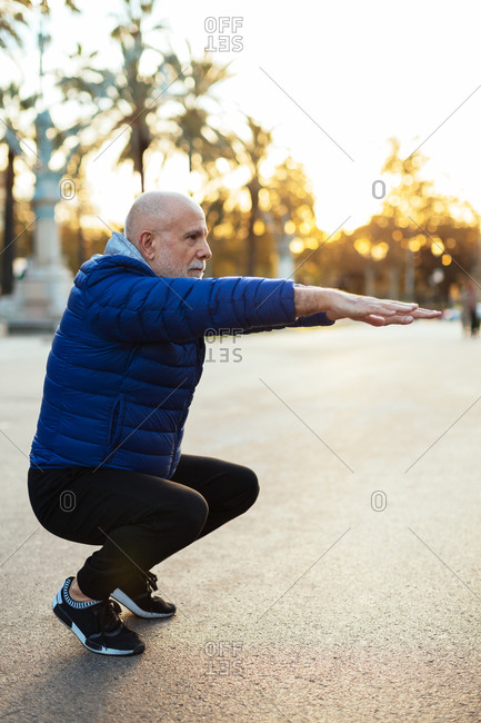 Senior man stretching on the street in autumn.