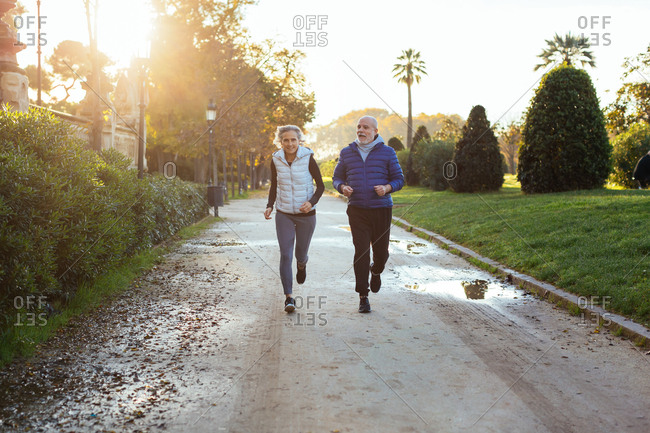 Senior couple running on the street in autumn.