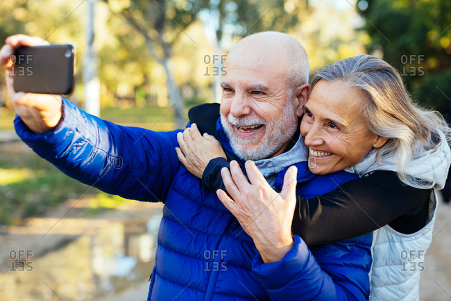 Smiling senior couple taking a selfie on the street.