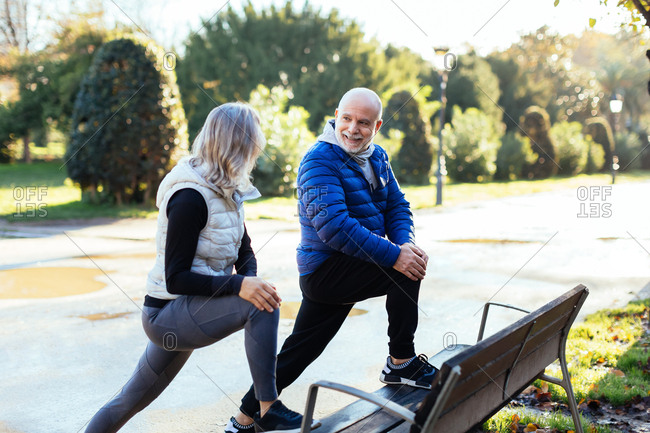 Senior couple stretching on the street in autumn.