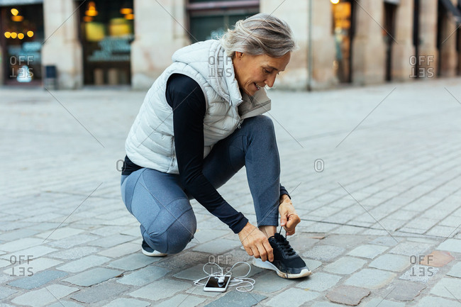 Senior woman tying her sneakers on the street.