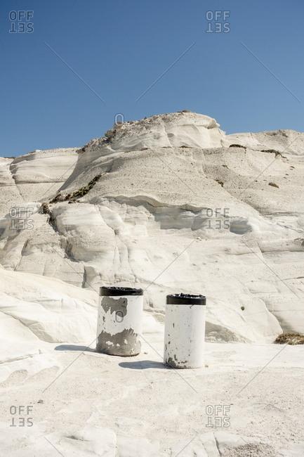Trash cans on rock formation at Sarakiniko beach, Milos, Cyclades, Greece