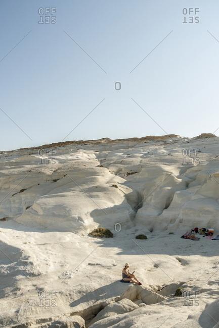 Milos, Cyclades, Greece - July 21, 2018: Woman relaxing at Sarakiniko beach