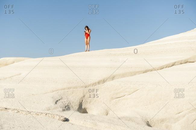 Woman on top of hill at Sarakiniko beach, Milos, Cyclades, Greece