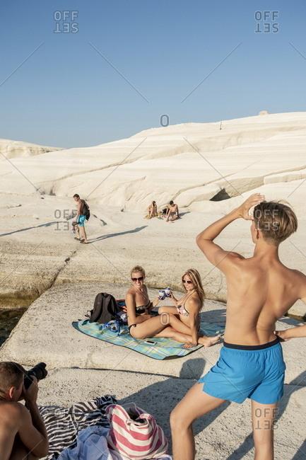 Milos, Cyclades, Greece - July 21, 2018: Young tourists on Sarakiniko beach