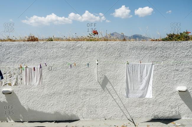 White stucco wall behind clothesline, Adamas, Milos, Cyclades, Greece