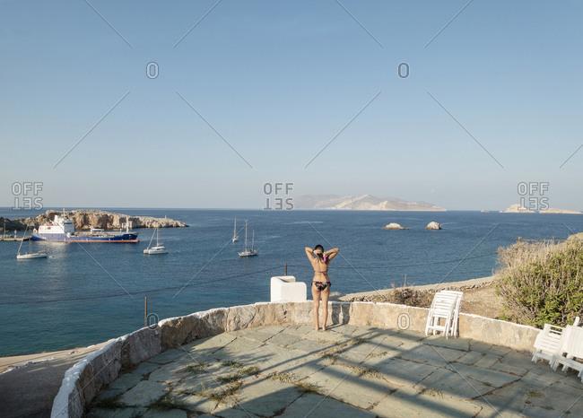 Woman in bathing suit overlooking the sea in Greece