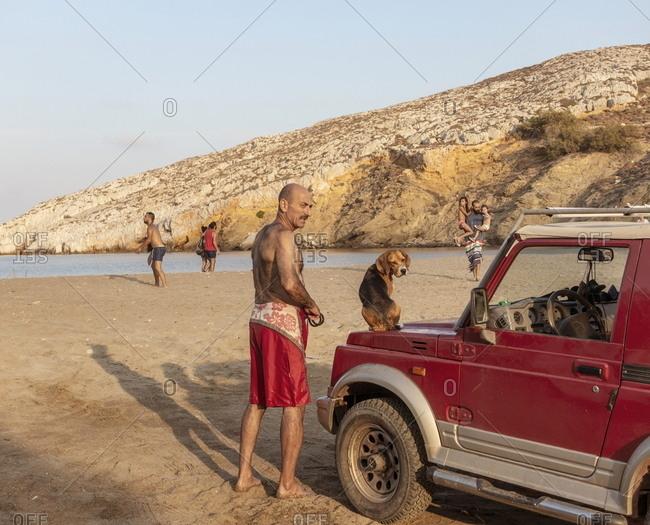 Folegrandos, Cyclades, Greece - July 26, 2018: Man standing by car with dog on hood