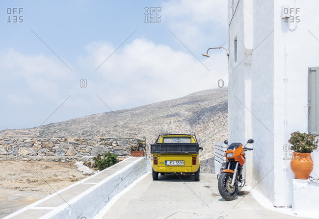 Amorgos, Chora, Cyclades, Greece - August 4, 2018: Yellow car beside orange motorcycle