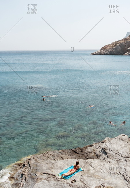 Amorgos, Cyclades, Greece - August 4, 2018: People swimming and sunbathing at Mouros beach