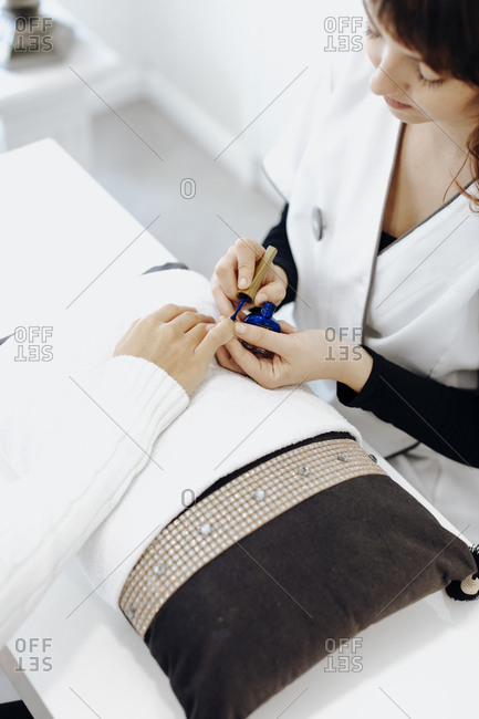 Woman receiving manicure with blue nail polish