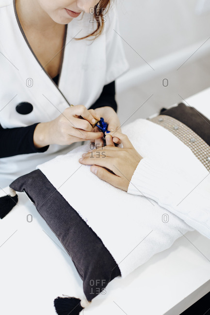 Woman getting manicure with blue nail polish