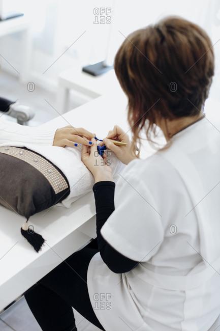 Nail tech painting a woman's nails blue