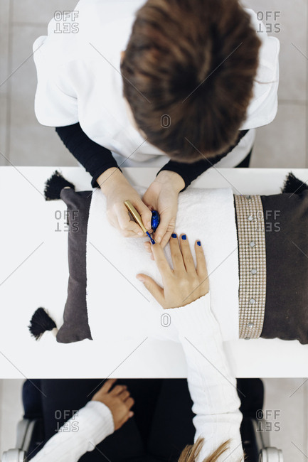Overhead view of woman receiving manicure with blue nail polish
