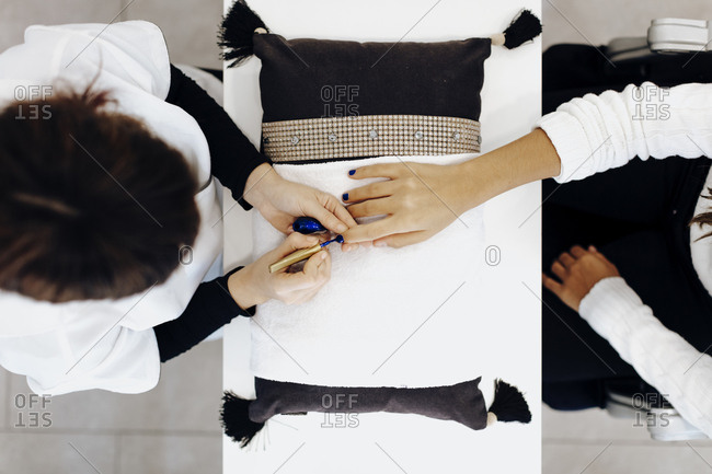Overhead view of nail tech painting a woman's nails blue