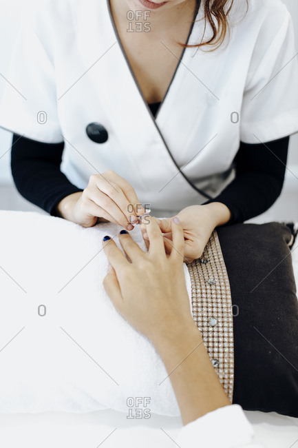 Nail tech removing polish from a woman's nails in a spa