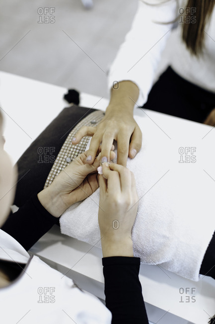 Nail tech removing polish from a woman's nails