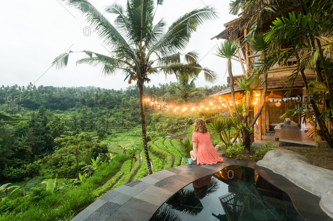 Woman sitting on edge of pool overlooking landscape in Bali