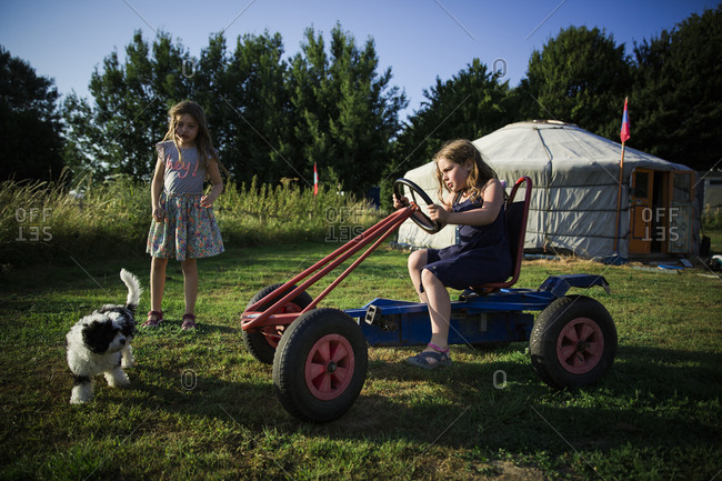Girl playing on a go cart with her sister and dog at a campground with a yurt