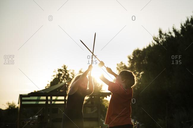Children pretending to fight with sticks