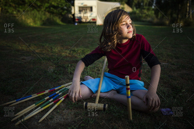 Boy sitting on the lawn at campground setting up croquet game