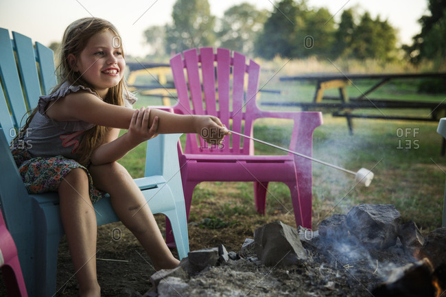 Smiling girl roasting a marshmallow over a campfire