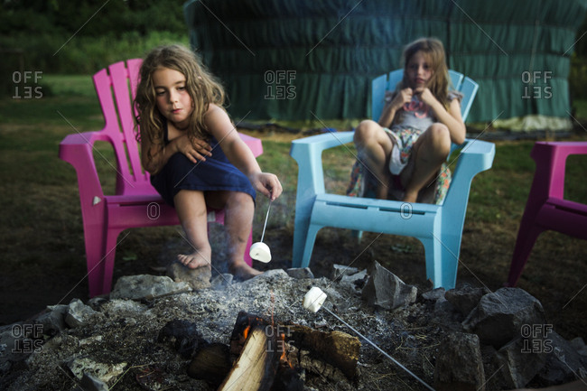 Girls roasting marshmallows over a campfire