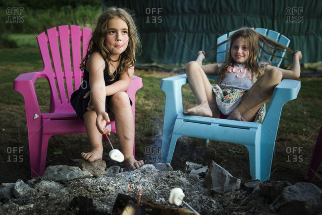 Girls sitting in camping chairs roasting marshmallows over a campfire