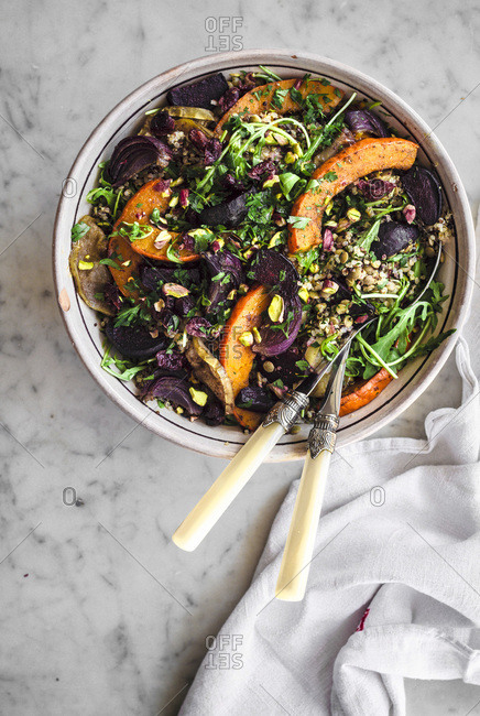 Quinoa lentil salad with rucola, roasted beets, pumpkin, apple, and red onion