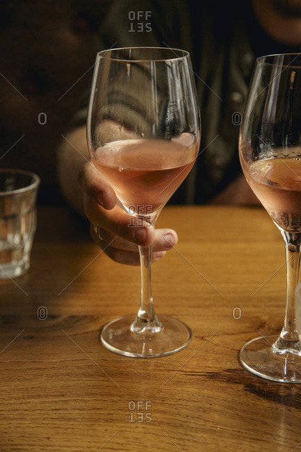 A glass of chilled rose wine in male hand
