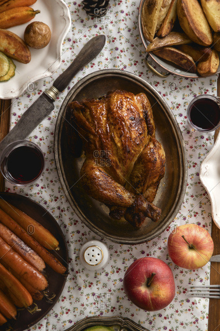 Traditional festive dinner with roasted chicken, apples and various garnishing on wooden table, covered with patterned tablecloth