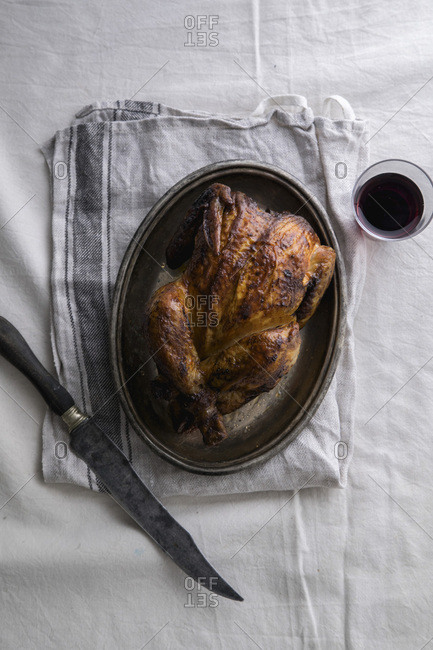 Roasted chicken on metallic tray with a knife and a glass of wine. Background of linen tablecloth