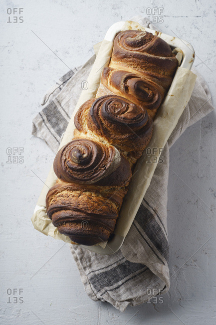 Swirl bread loaf in baking pan on white concrete background