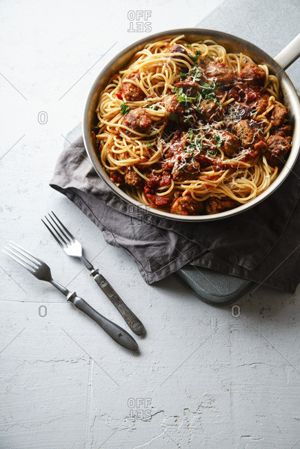 Spaghetti with meatballs, tomato sauce, parsley and cheese served in a pan on white concrete background