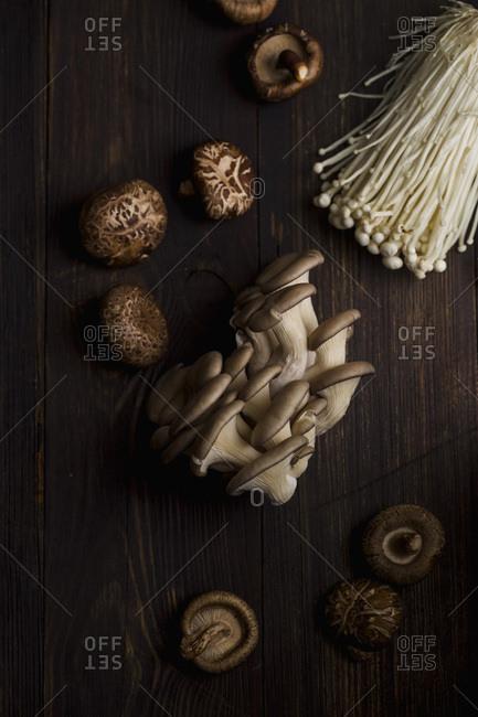 Various raw mushrooms on old wooden table. Enoki, shiitake and oyster mushrooms