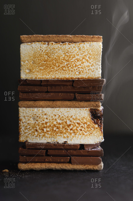 A stacked smores with toasted marshmallows still steaming. On a dark background with dramatic natural light.