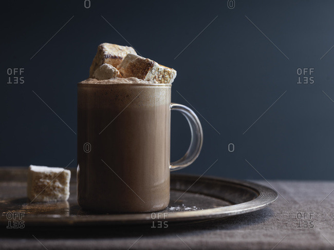 A glass of hot cocoa with homemade marshmallows spilling out the top. Moody image with a dark blue wall in the background. Natural light.