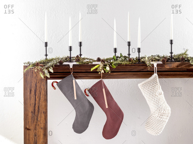 A large, wood mantle with 3 Christmas stockings hanging with candy canes and holiday decor. Bright, natural light on a textured, white concrete wall.