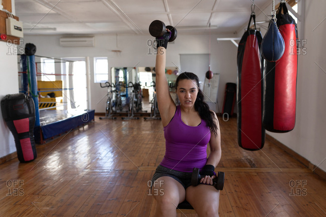 Young female boxer exercising with dumbbell in fitness studio