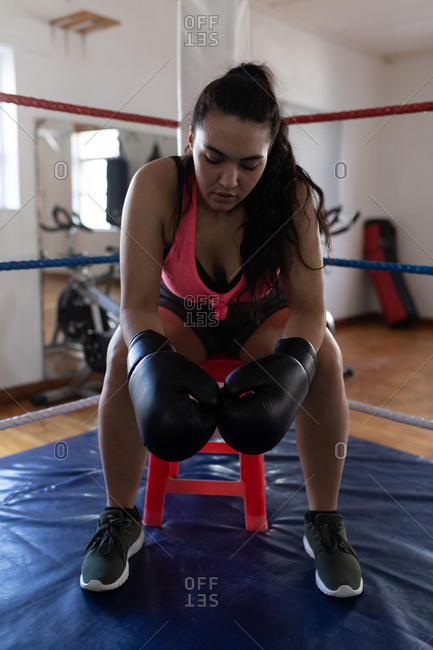Young female boxer relaxing in fitness studio